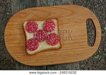 Sandwich Of Sausage Salami And Bread On A Wooden Board