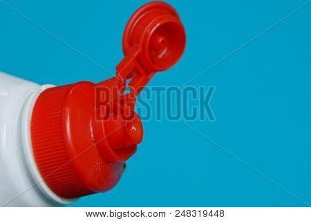 Red Open Plastic Stopper On White Bottle