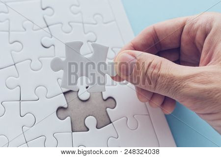 Man Successfully Solving Jigsaw Puzzle, Hand Putting A Missing Piece To Complete The Solution