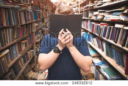 Portrait Of A Man Standing In The Library Covers His Face With An Open Black Book. A Man Hiding Behi