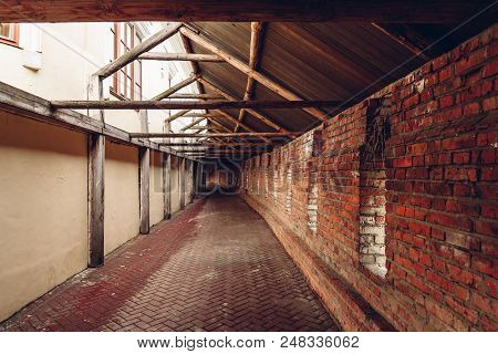 Old City Hidden Passageway With Embrasures In Brick Wall.