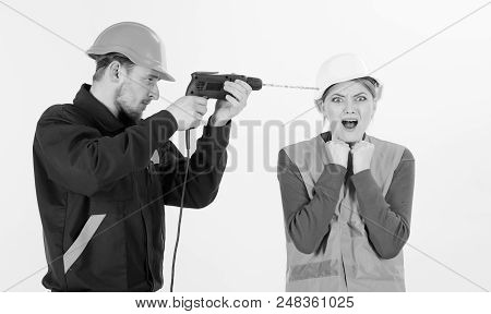 Builder, Repairman Makes Hole In Female Head. Headache Concept. Woman With Screaming Face In Helmet,
