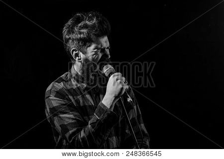 Musician, singer makes effort to win musical contest. Man with tense face holds microphone, singing song, black background. Musician with beard and mustache lighted by spotlight. Talent show concept. poster