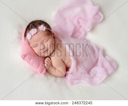 Cute sleeping newborn baby girl in a pink