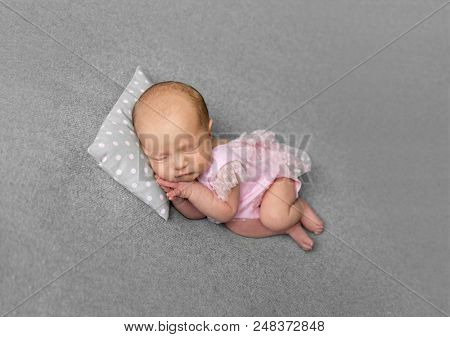 Lovely newborn girl in pink dress sleeping with pillow under her little head. Little princess with flowery hair band sleeping on her side