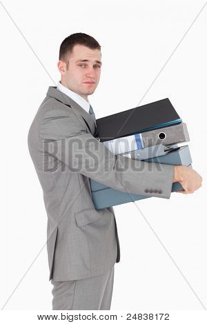 Portrait of a stressed businessman holding a stack of binders against a white background