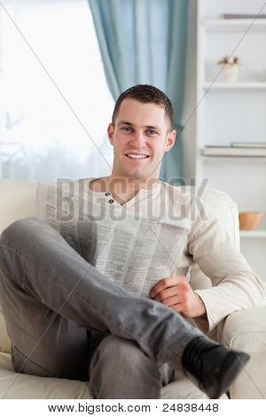 Portrait of a smiling man reading a newspaper in his living room