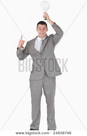 Portrait of a businessman holding a bulb above his head while pointing at something against a white background
