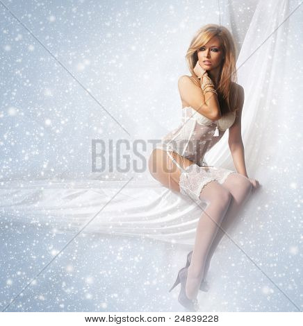 Portrait of young and attractive girl in sexy lingerie over winter background