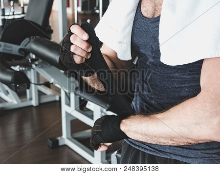 Stylish, Muscular Man With A White Towel On His Shoulders And Black Sports Gloves, Preparing For Str