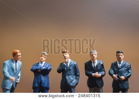 Miniature People Businessman Standing On Wooden Background , Concept Of Business Leader And Teamwork