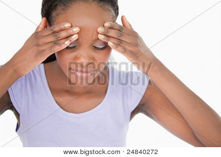 Close up of young woman rubbing her temples against a white background