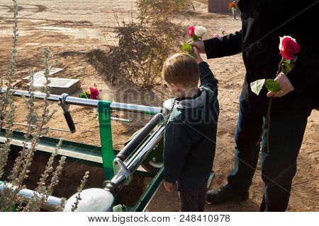 A Father And Son Say Goodbye To A Loved One By Throwing Roses Into An Open Grave During A Burial At