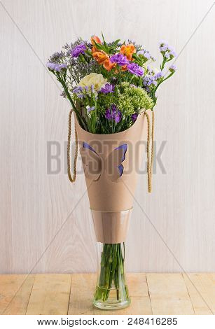 A Beautiful Bouquet Of  Blooming Flowers Wrapped In Paper In Crystal Glass On Wooden Table. Wood Bac