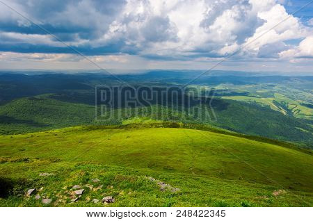 Grassy Hillside View From Above. Beautiful Summer Landscape Of Mountainous Area. Huge Clouds A Brigh