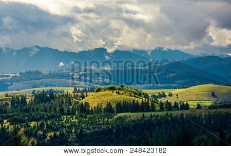Hilly Countryside On A Cloudy Day. Wonderful Landscape In Early Autumn. Dark Blue Mountain Ridge In