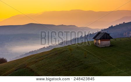 Woodshed On A Hillside At Sunrise. Beautiful Countryside Scenery Of Mountainous Area. Yellow Sky Ove