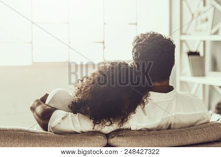 Young Pakistani Couple In White Clothes Sitting On Gray Sofa And Hugging. Arabic Woman And Man. Youn