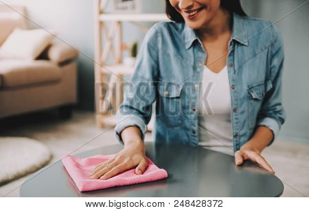 Close up. Young Girl Cleaning Table with Duster at Home. Young Happy Janitor with Cleaning Equipment near White Window. Woman in Shirt with Duster. Room Cleaning Concepts. Home Routine Concepts. poster