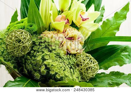 Close-up Bouquet Of Blooming Green Flowers In The Crystal Glass On Wooden Background, Dark Table. Tr