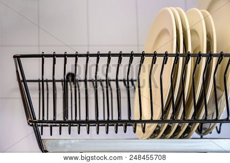 White Dishes Drying On Metal Dish Rack. Dish Drying Rack. The Dryer Is Fixed Horizontally On The Wal