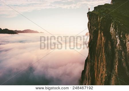 poster of Traveler standing on cliff edge mountain top above sunset clouds travel adventure lifestyle summer journey vacations