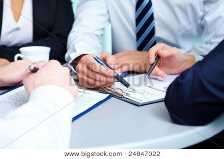 Image of human hands during discussion of business plan at meeting