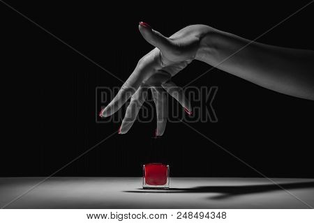 Hand With Red Manicure And Nail Polish Bottle. Black And White