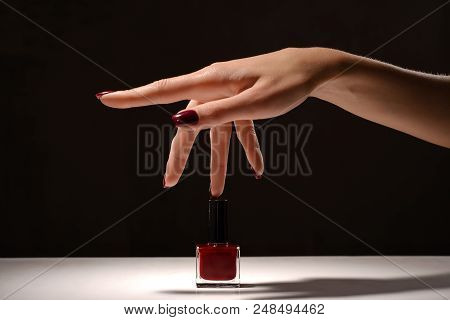 Female Hand With Red Manicure And Nail Polish Bottle. Black And White