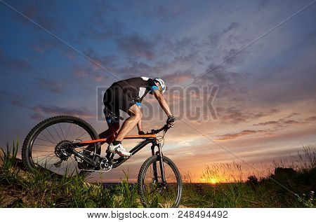 Robust And Sporty Man In Helmet And Black Sportswear Sitting On Bicycle And Cycling. Energetic Cycli