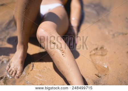 Close Up Legs With Wet Sand On Them, Of A Lady In Yellow And White Bikini Lies Down On Wet Sand In S