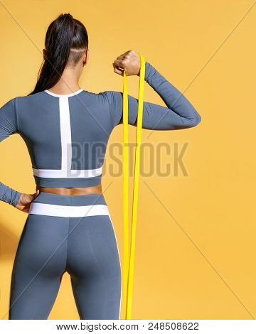 Fitness Girl Performs Exercises For The Muscles Of The Hands With Resistance Band. Photo Of Latin Gi