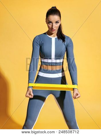 Sporty Woman Performs Exercises For The Muscles Of The Hands. Photo Of Woman Workout With Resistance