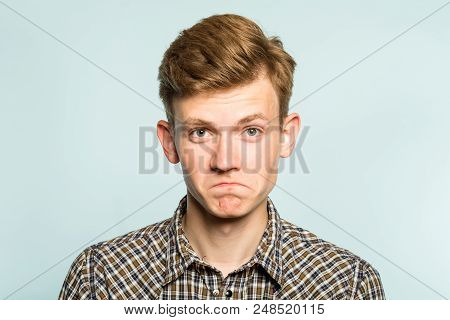 Not Bad. Approval Judgement. Accepting Facial Expression. Portrait Of A Young Man On Light Backgroun