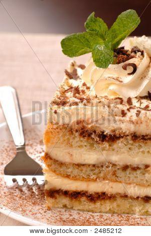Creamy Tiramisu With Mint On A White Plate