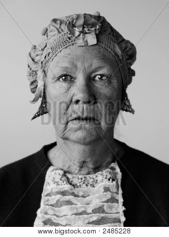 Dour senior woman in the studio wearing a vintage hat and lace. poster