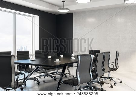 Side View On Black Meeting Table And Chairs In Modern Conference Room With Concrete Wall And Floor.