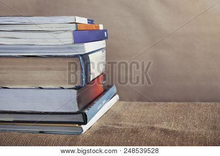 Different Size Of Unorganized Of Textbook Stack On The Table With Sackcloth Cover, University Study