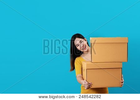Portrait Of Young Asian Entrepreneur Happy Smiling And Holding Or Carrying Pile Of Boxes In Hands Wi
