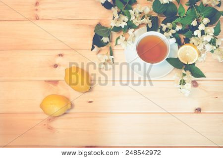 Green Tea, Lemon And Jasmine Flowers On Wooden Background. Top View, Copy Space. Toned Image.