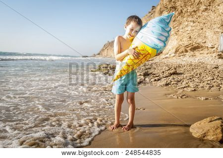 Cute And Tender Little Caucasian Baby Boy Hugging An Ice Cream Cone Balloon At The Seaside On A Sunn