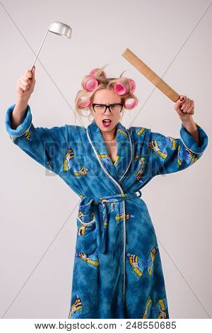 Screaming Angry Housewife In A Dressing Gown And Curlers With A Ladle In Her Hand.