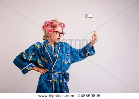 Screaming Housewife In A Dressing Gown And Curlers With A Ladle In Her Hand.