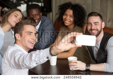 Diverse Colleagues Taking Group Photo On Smartphone Spending Time Together In Coffeeshop, Smiling Mu