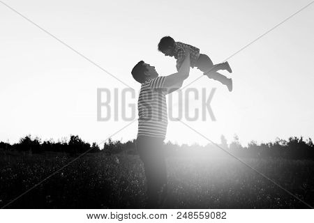 Father And Son Playing In The Park At The Sunset Time. Happy Family Having Fun Outdoor.