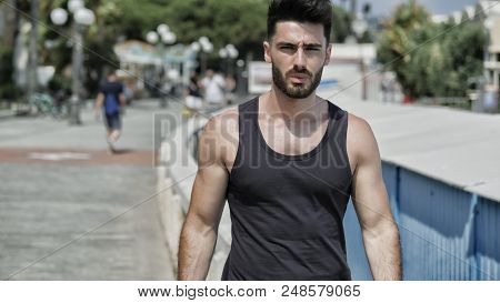 Attractive Fit Athletic Young Man Soaking In The Sun On Seaside Boardwalk Or Seafront, Wearing Black