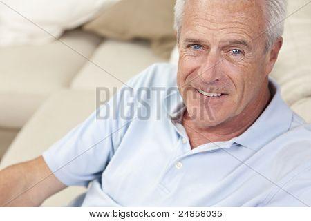 Glückliches und gesundes Alter Mann sitzen auf einem Sofa zu Hause lächelnd und glücklich