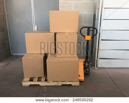 Pallet jack stacked high with cardboard box from delivery to warehouse