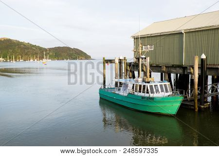 Charter Fishing Vessel Tied Up At Mangonui Wharf Harbour With Anchored Boats In Background, Far Nort