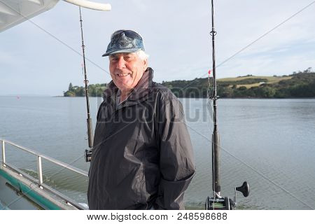 Active Retirement - Portrait Of A Retired Senior Male Tourist On A Fishing Charter Boat At Mangonui,